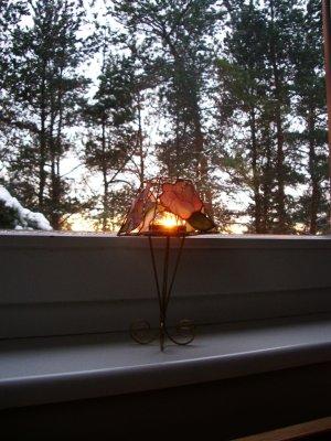 Aken, küünlajalg ja lumiste puude taha loojuv päike